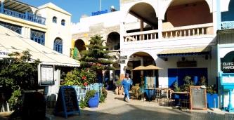 """Piazzetta di Essaouira: """"Il viaggio è una specie di porta attraverso la quale si esce dalla realtà come per penetrare in una realtà inesplorata che sembra un sogno"""". (Guy de Maupassant)."""